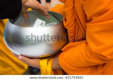People putting food offerings in alms bowl with Buddhist monk or novice for make merit, Buddhist holy day
