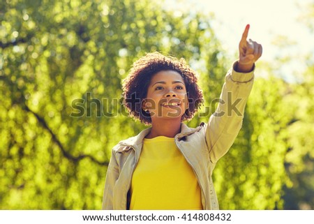 people, race, ethnicity and gesture concept - happy african american young woman pointing finger in summer park - stock photo