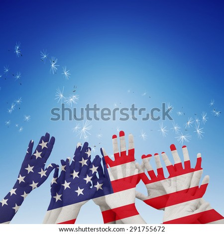 People raising hands in the air against digitally generated dandelion seeds against blue sky - stock photo