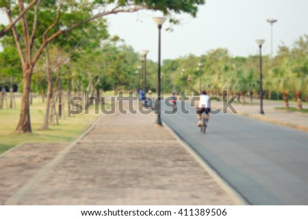 People relax by cycling and running in park and garden with blurred view - stock photo