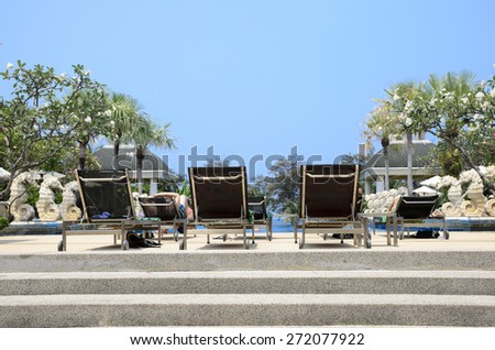 People relaxation on sun loungers by swimming pool / sunbathing