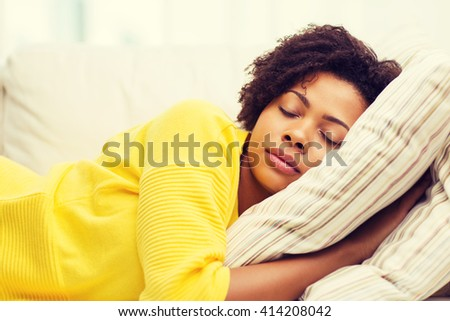 people, rest, comfort and leisure concept - african american young woman sleeping on sofa at home - stock photo