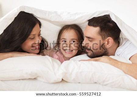 people, rest, love, relationships and happiness concept - happy family lying in bed under blanket at home