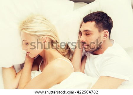 people, rest, relationships and happiness concept - happy couple of man and woman sleeping in bed