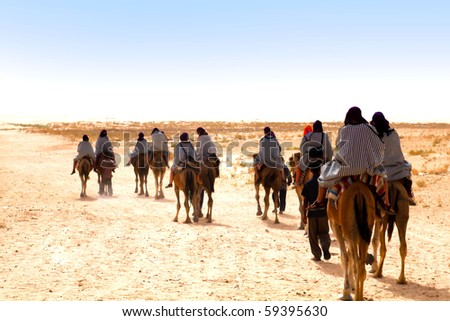 People ridding by camels on the Sahara desert - stock photo