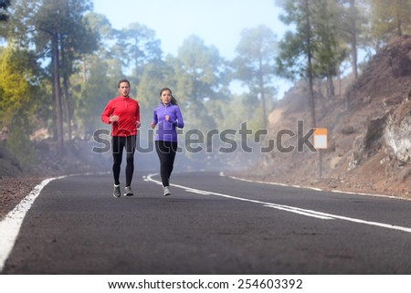People running - athlete runners training jogging in cloudy and cold weather. Exercising runner couple working out living healthy lifestyle training for marathon together on mountain road. - stock photo