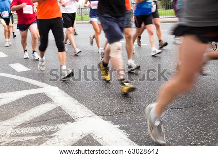 People running in marathon on a street in intentional motion blur - stock photo