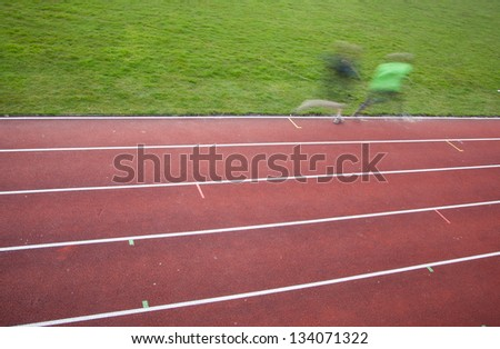 people running on race track in motion blur - stock photo