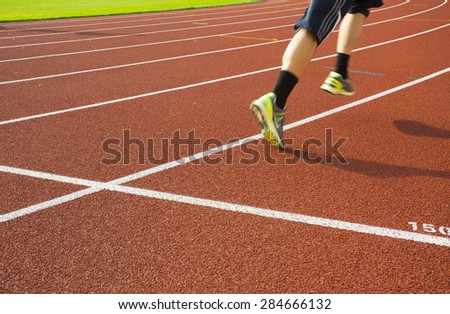 people running on track in sunset - stock photo