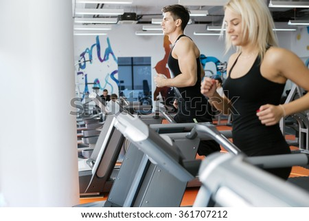 People running on treadmills in gym to keep body in shape - stock photo