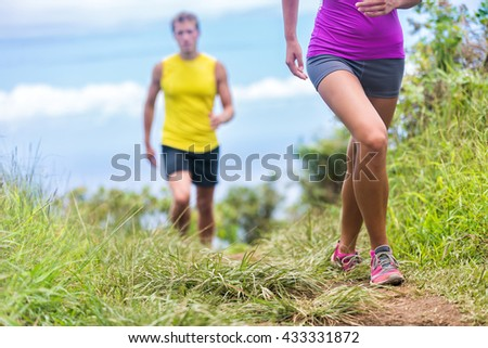 People running walking in nature on trail path. Group of runners hikers hiking in summer outdoors. Woman legs and man in the background. Fitness activity for a fit couple living a healthy lifestyle.