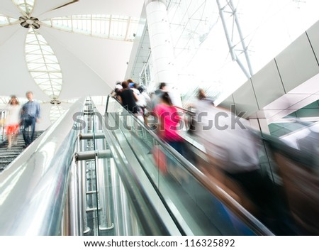 People rush on escalator motion blurred. shopping abstract. - stock photo