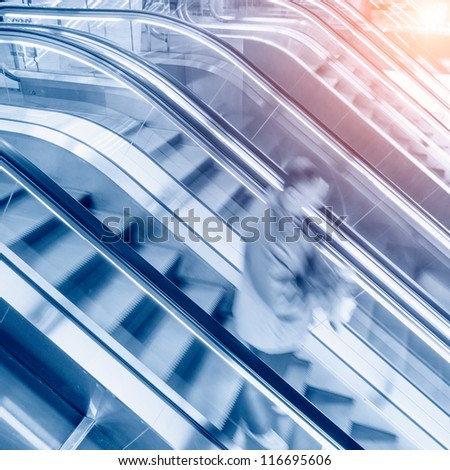 People rush on escalator motion blurred. shopping abstract - stock photo