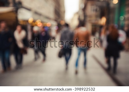 People rush on the street. Blurred crowd of different people are walking in the city. Defocused background of city life. Evening with lights. - stock photo