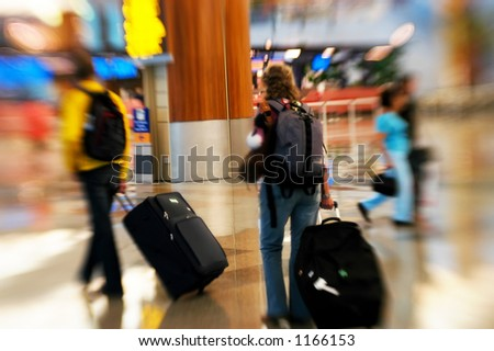 People rushing in an airport. Shot with a special effect lens. Intentional blur & selective focus. - stock photo