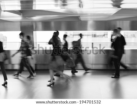 People rushing in the lobby. Motion blur. - stock photo