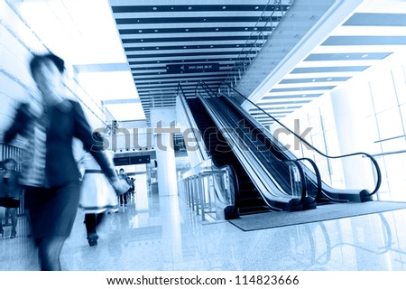 People rushing on escalator in business center, mall or airport to work,  with motion blur . - stock photo