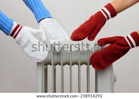 people's hands in mittens bask near a radiator on a white background - stock photo