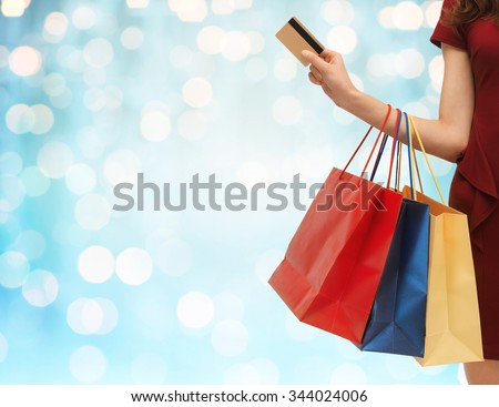 people, sale and consumerism concept - close up of woman with shopping bags and bank or credit card over blue holidays lights background - stock photo