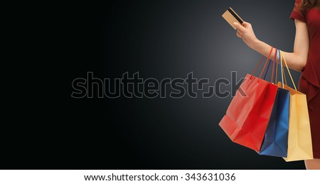 people, sale, black friday and consumerism concept - close up of woman with shopping bags and bank or credit card - stock photo