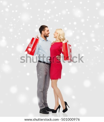 people, sale, christmas, winter and holidays concept - happy couple with red shopping bags hugging and talking over snow background