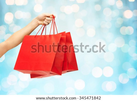 people, sale, consumerism, advertisement and commerce concept - close up of hand holding red blank shopping bags over blue holidays lights background - stock photo