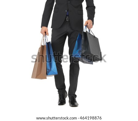 people, sale, fashion and consumerism concept - close up of man in suit with shopping bags