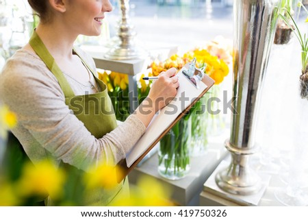 people, sale, retail, business and floristry concept - close up of happy smiling florist woman with clipboard writing and making notes order at flower shop - stock photo