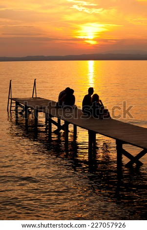 people sat on jetty watching the sunset silhouette  - stock photo