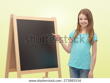 people, school, children, advertisement and education concept - happy little girl with blackboard and chalk over yellow background - stock photo