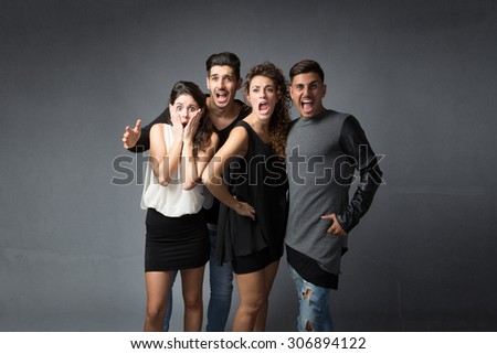 people screaming with open mouth, dark background - stock photo