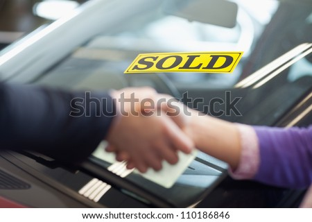 People shaking hands in front of a sold car - stock photo