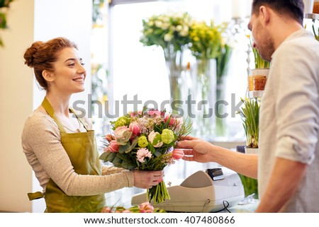 people, shopping, sale, floristry and consumerism concept - happy smiling florist woman making bouquet for and man or customer at flower shop - stock photo