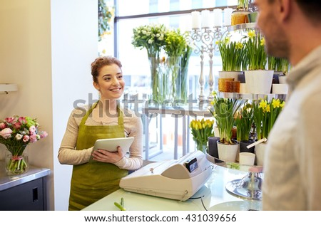 people, shopping, sale, floristry and consumerism concept - happy smiling florist woman with tablet pc computer and man or customer at flower shop - stock photo