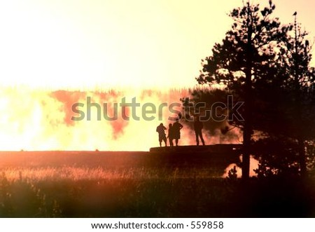 People silhouetted against sunset lit mist of Grand Prismatic Hot Spring in Yellowstone National Park, Wyoming - stock photo