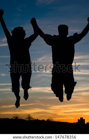 People silhouettes at sunset a clear summer night - stock photo