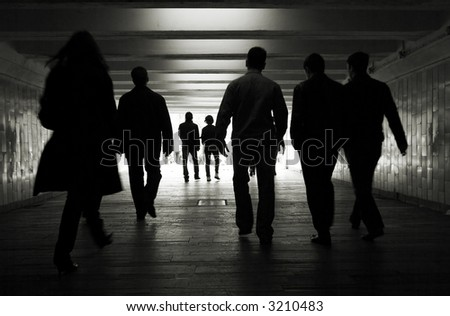 People silhouettes in a subway tunnel - stock photo