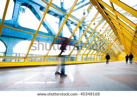 People silhouettes in motion in yellow passage - stock photo
