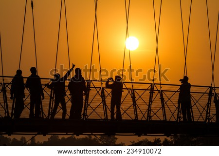 People silhouettes on the sunset on Lakshman Jhula bridge over Ganges in Rishikesh, India. - stock photo
