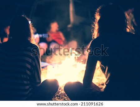 People sit at night round a bright bonfire - stock photo