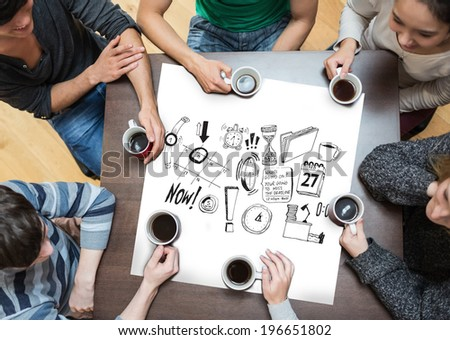 People sitting around table drinking coffee with page showing brainstorm graphic