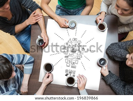 People sitting around table drinking coffee with page showing idea and innovation graphic - stock photo