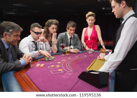 People sitting at table playing poker in a casino - stock photo