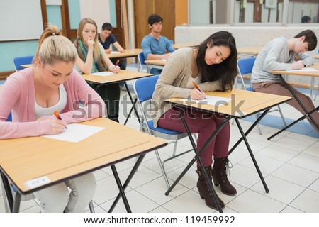 People sitting at the classroom while writing - stock photo