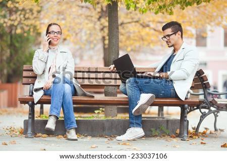 People sitting on a bench using mobile phone and laptop - stock photo