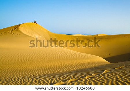 People sitting on a mountain of sand in the desert in Gran Canaria - stock photo