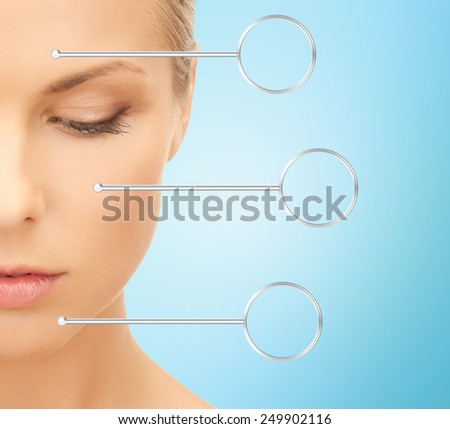 people, skin care and beauty concept - close up of beautiful young woman half face over blue background - stock photo