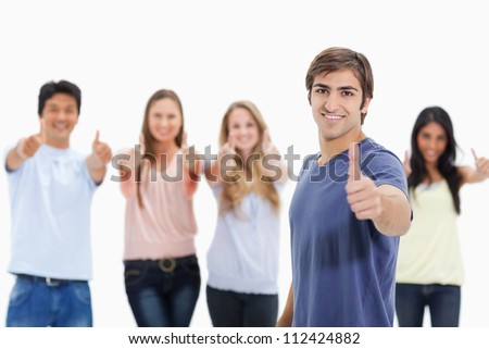 People smiling and approving with one of them in foreground against white background - stock photo