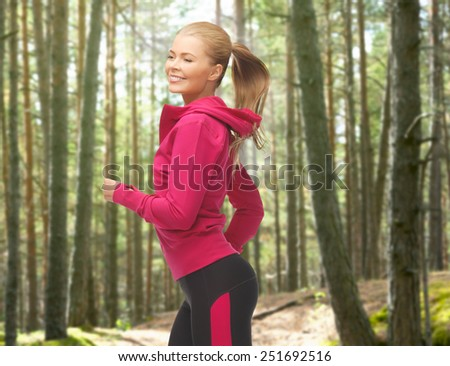 people, sport, fitness and slimming concept - happy woman running or jogging over woods background - stock photo