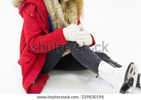 people, sport, trauma, pain and leisure concept - close up of young woman fell down on skating rink with knee injury holding to her leg